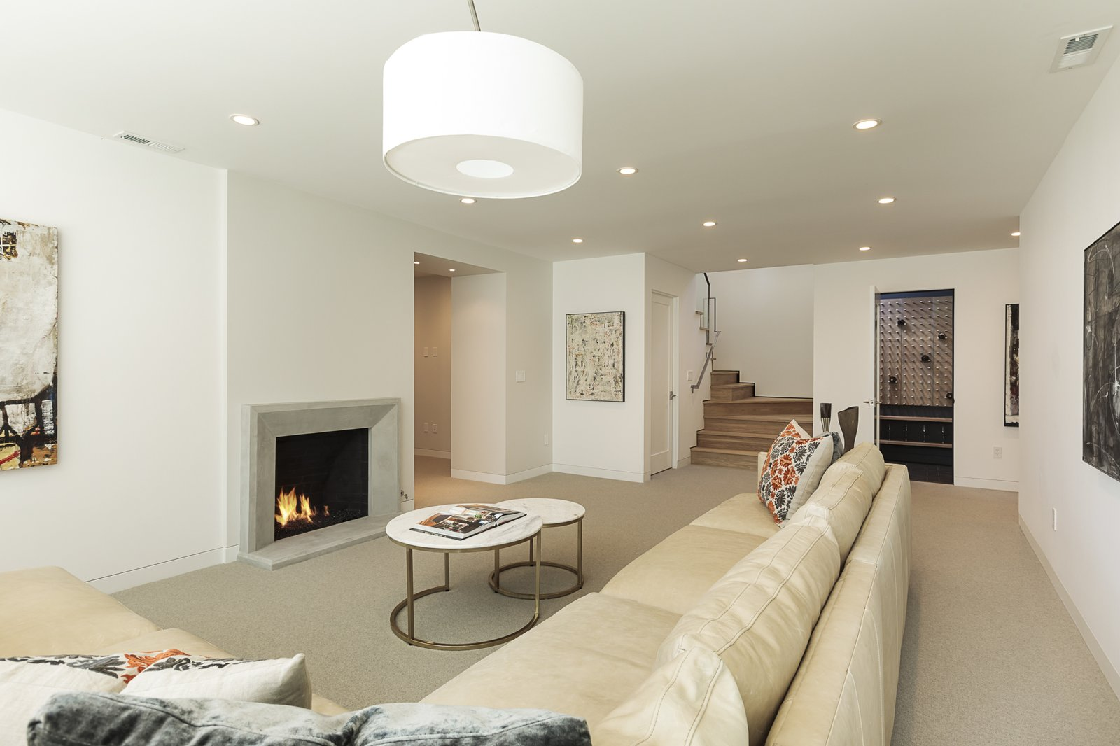 Living Room, Sectional, Coffee Tables, Recessed Lighting, Floor Lighting, Carpet Floor, and Standard Layout Fireplace This view shows the space from another angle. The door at the bottom of the staircase leads to the laundry area. The door to the right of the staircase goes to a modern wine cellar with a sleek mounted wine rack from Stact.   Photo 23 of 24 in An Iconic Portland Midcentury Is Seeking a New Owner For $1.6M