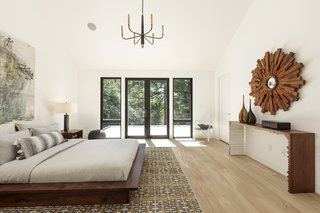 A candelabra-style pendant hangs from the ceiling of this midcentury bedroom in Portland.
