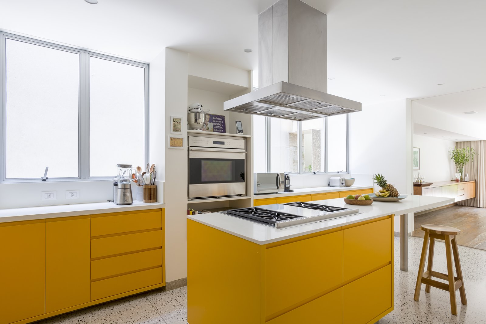 Kitchen, Recessed Lighting, Terrazzo Floor, Range Hood, Range, Colorful Cabinet, and Wall Oven Bright yellow cabinets in the kitchen add a playful, fun touch, while also maintaining to same sleek, contemporary look.     Photo 9 of 13 in Lush Gardens Infuse Tropical Vibes in This Chic Brazilian Home