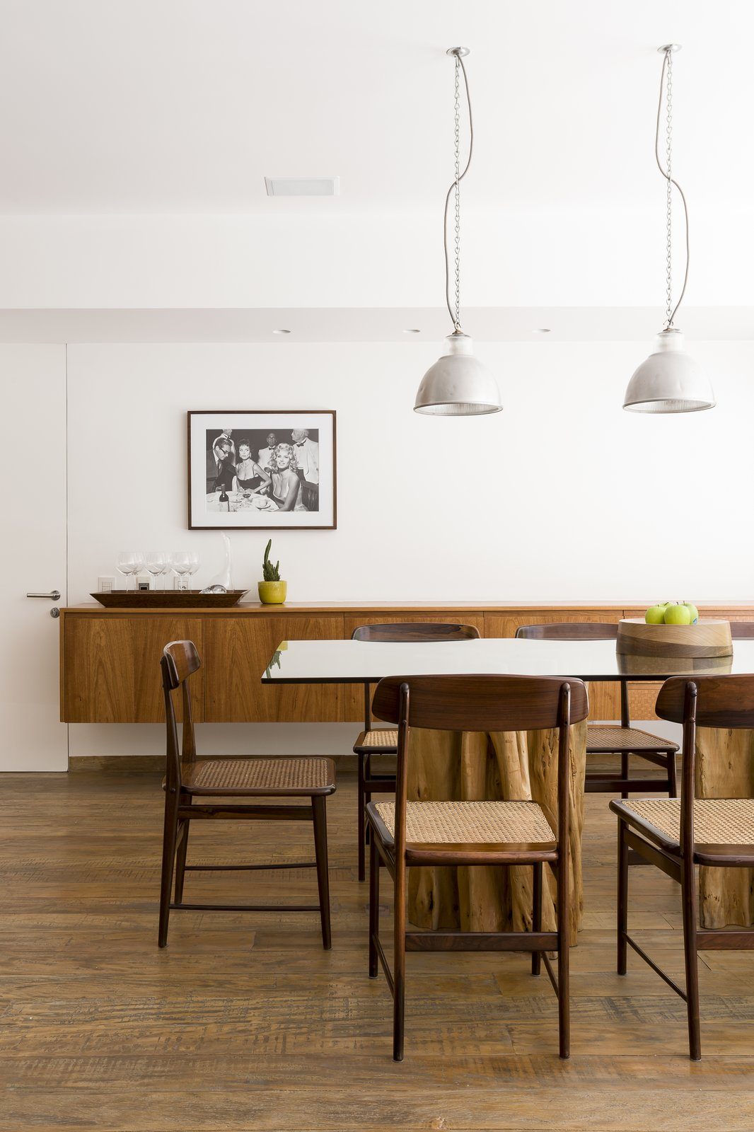 Dining Room, Pendant Lighting, Table, Medium Hardwood Floor, Chair, Recessed Lighting, and Bar The use of different woods and textures contrast beautifully with one another.      Photo 8 of 13 in Lush Gardens Infuse Tropical Vibes in This Chic Brazilian Home