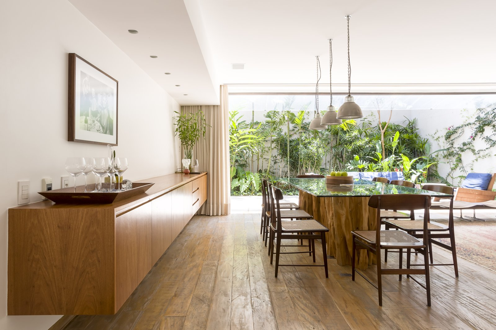 "Dining Room, Chair, Table, Medium Hardwood Floor, Pendant Lighting, Rug Floor, Bar, and Recessed Lighting ""We maximized natural lighting, ventilation, and contact with the outdoors in all environments, which sometimes open onto the street at the height of the treetops, or opens onto an outdoor area with a tropical garden,"" explains the architects.     Photo 7 of 13 in Lush Gardens Infuse Tropical Vibes in This Chic Brazilian Home"