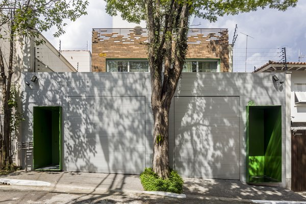 From the street, a discrete metallic wall features two green steel doors on either side.