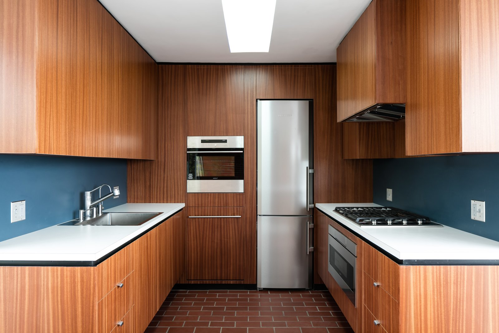 Kitchen, Range Hood, Laminate, Terra-cotta Tile, Ceiling, Drop In, Refrigerator, Wood, Cooktops, and Wall Oven A look at the kitchen.  Best Kitchen Cooktops Range Hood Refrigerator Drop In Ceiling Photos from Craig Ellwood's Iconic Smith House in L.A. Is Listed For $3M
