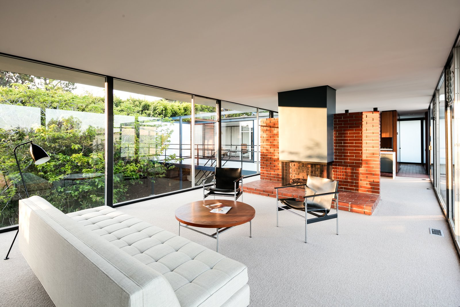 Living, Sofa, Chair, Standard Layout, Carpet, Coffee Tables, and Floor A look at the open living plan. Note the fireplace is set in the center of the space against a brick dividing wall.     Best Living Standard Layout Carpet Photos from Craig Ellwood's Iconic Smith House in L.A. Is Listed For $3M
