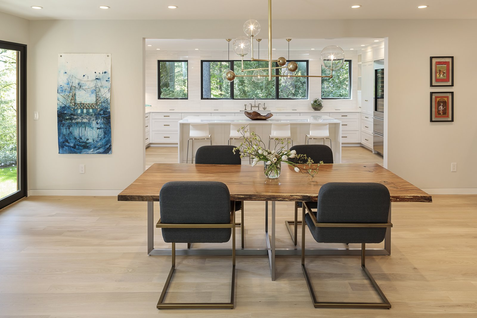 Dining Room, Table, Pendant Lighting, Chair, Light Hardwood Floor, Recessed Lighting, and Stools Silver opened the kitchen to the dining room, creating the sense of one big space with a seamless flow. He also inserted sliding doors to an exterior patio.   Photo 12 of 24 in An Iconic Portland Midcentury Is Seeking a New Owner For $1.6M