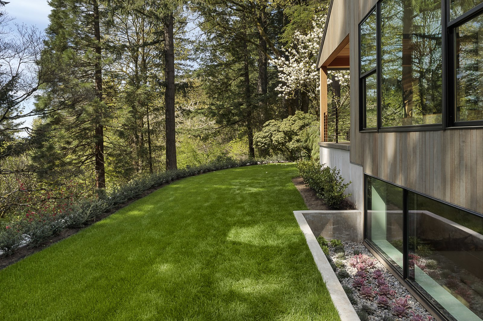 Exterior, House Building Type, Wood Siding Material, Gable RoofLine, Metal Roof Material, and Concrete Siding Material An exterior shot of the atrium with the succulents.  Photo 24 of 24 in An Iconic Portland Midcentury Is Seeking a New Owner For $1.6M