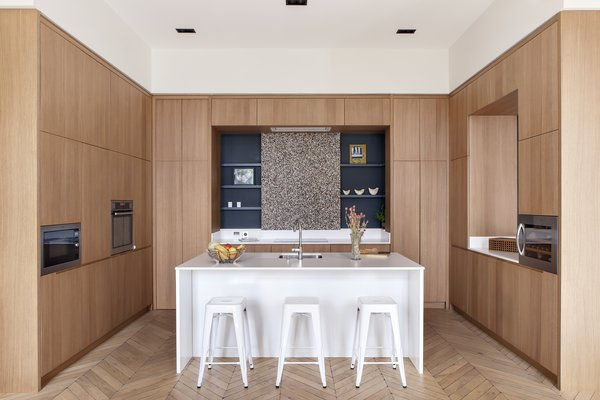 The kitchen sits comfortably between a dining area, a large reading room, and an informal space for the kids.