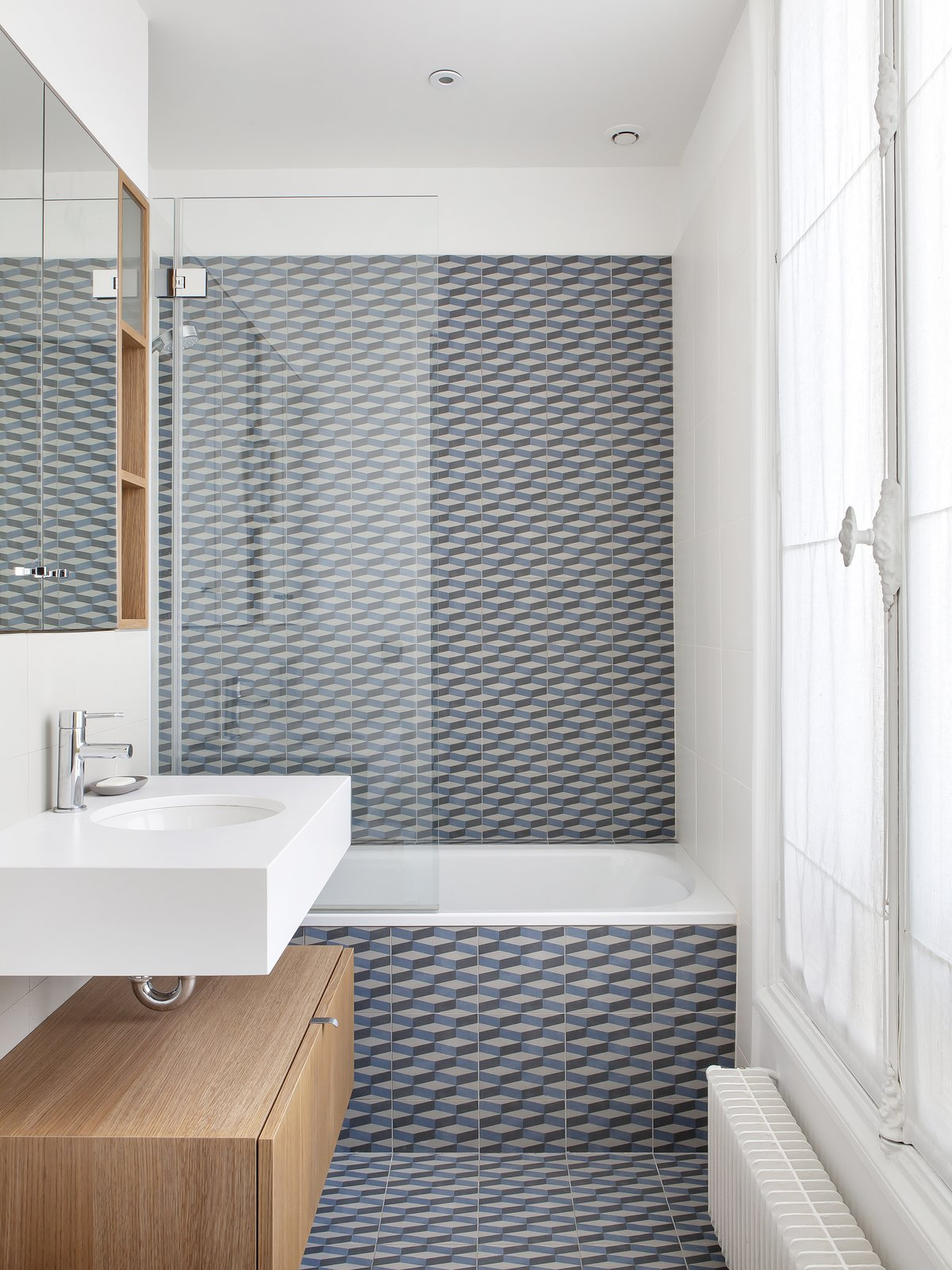 Bath, Soaking, Enclosed, Recessed, Porcelain Tile, Wall Mount, Alcove, and Undermount The children's bathroom features Mutina's azulej cubo grigio floor and wall tiling.  Best Bath Enclosed Wall Mount Recessed Photos from A Parisian Abode Is Reborn With a Fresh, Unexpected Color Palette