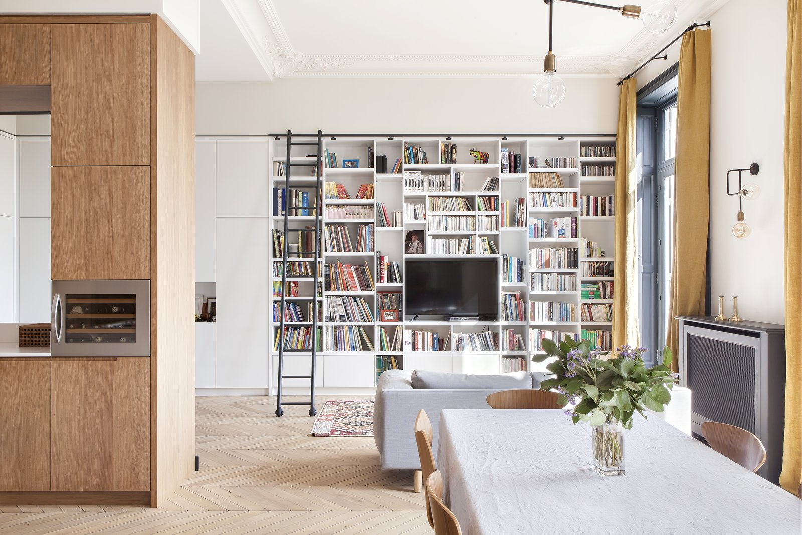 Dining, Chair, Table, Pendant, Medium Hardwood, Shelves, and Standard Layout A wall of bookshelves with a library ladder enriches the sitting area.  Best Dining Shelves Table Pendant Chair Medium Hardwood Photos from A Parisian Abode Is Reborn With a Fresh, Unexpected Color Palette