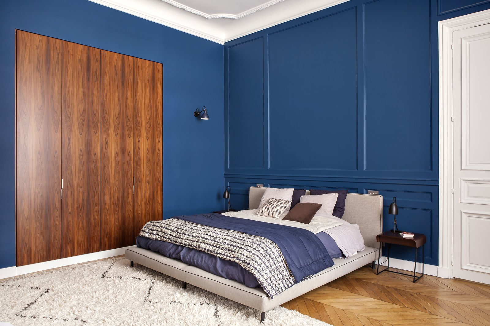 Bedroom, Rug, Night Stands, Storage, Medium Hardwood, Table, Wall, and Bed Bright and bold choices continue with the master bedroom. The walls have been painted a rich blue T0.30.20 from Sikkens.  Best Bedroom Medium Hardwood Storage Photos from A Parisian Abode Is Reborn With a Fresh, Unexpected Color Palette