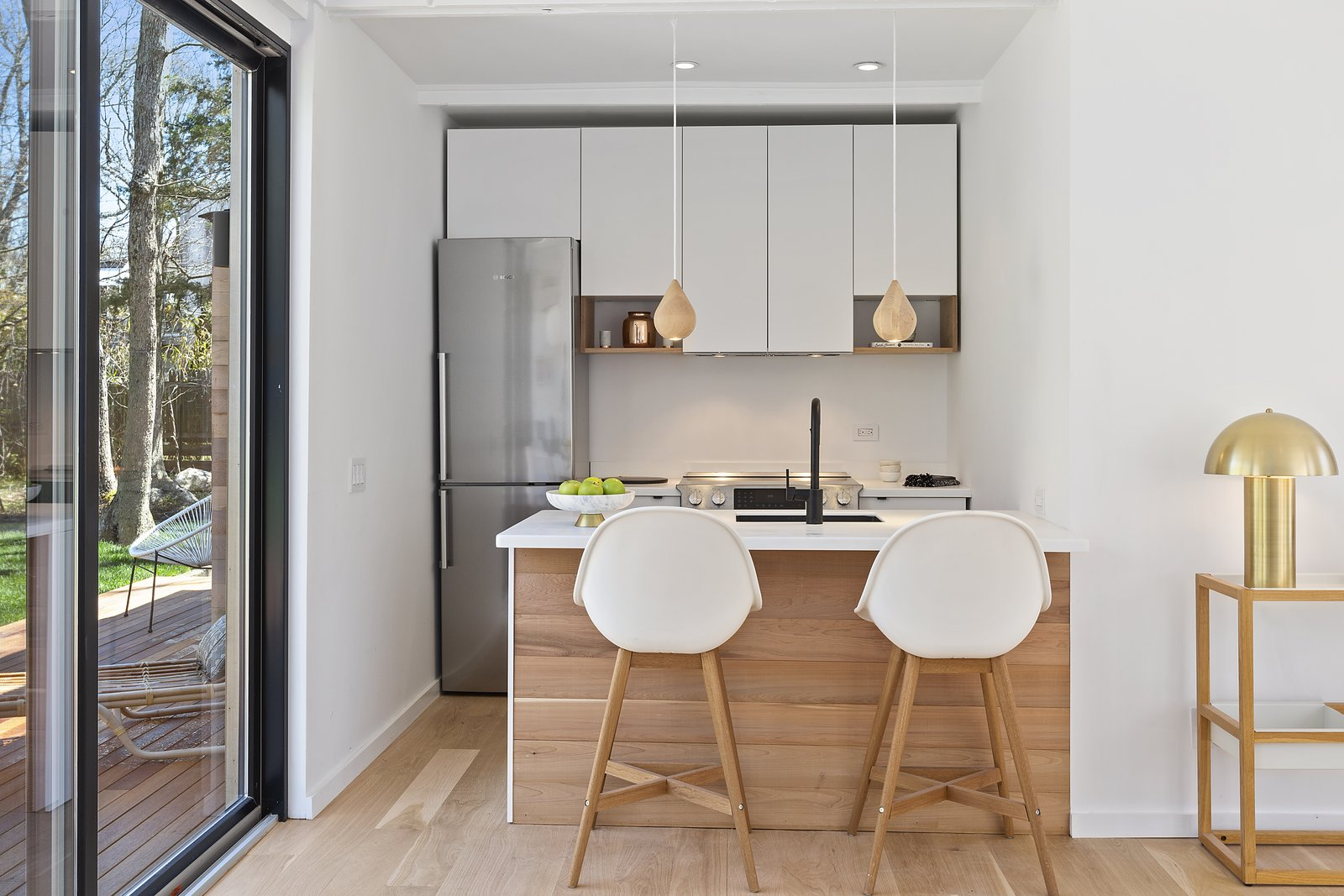 Kitchen, Refrigerator, Range Hood, White, Pendant, Light Hardwood, Range, Recessed, and Undermount The 1,000-square-foot dwelling has a petite yet highly efficient kitchen.    Best Kitchen Range Hood Light Hardwood Range Refrigerator White Undermount Photos from A Revamped Midcentury Wrapped in Glass and Timber Is Listed For $1.25M
