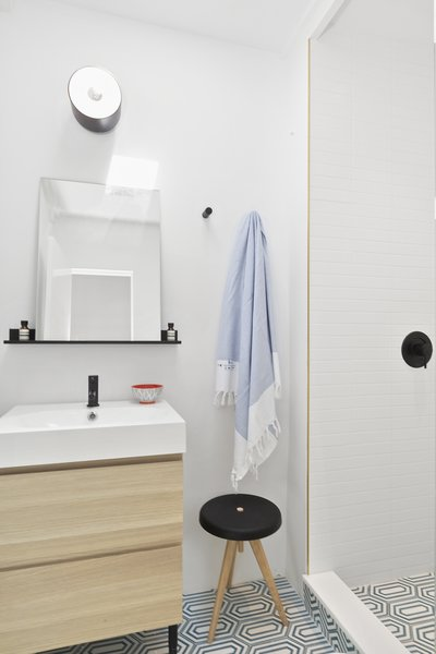 Luxury finishes in the bathroom include heated floors, Flos lights, Moen fixtures, and graphic tiles from Anne Saks.
