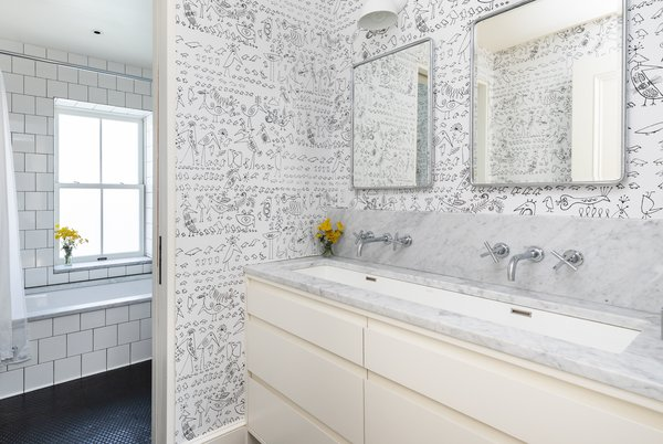 The fourth-floor hall bathroom has double faucets over a large trough sink, a custom vanity, and black penny-round tiled floors. A pocket door separates the sink area from the tub and toilet.