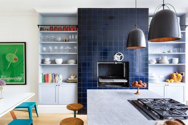 The pièce de résistance, however, is a one-of-a-kind Grillworks grill. Located in a refurbished wood-burning fireplace, it has been clad in striking tiles from Heath Ceramics and is flanked by open shelving.