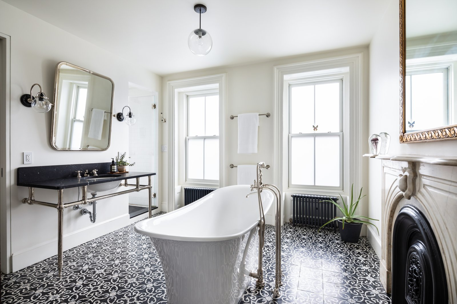 Bath, Freestanding, Wall Mount, Cement Tile, Pendant, Marble, and Wall A beautifully designed, light-filled bathroom features a deep Victoria + Albert freestanding tub, an original marble mantle, a large black marble-topped vanity, and an encaustic concrete-tiled floor.     Best Bath Pendant Wall Marble Photos from A Beautifully Restored Brooklyn Brownstone Is Listed at $4M