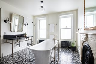 A beautifully designed, light-filled bathroom features a deep Victoria + Albert freestanding tub, an original marble mantle, a large black marble-topped vanity, and an encaustic concrete-tiled floor.
