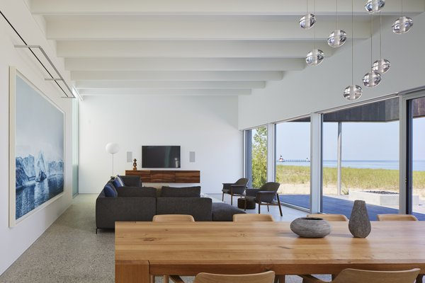 The open-plan living and dining area features a bright, expansive sense of space thanks to the wall of windows and the spectacular surrounding views.