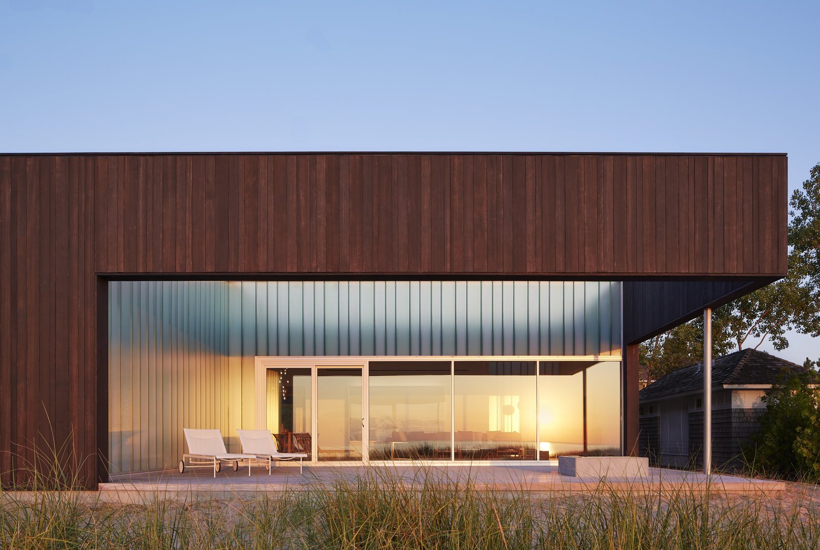 Exterior, Wood Siding Material, Flat RoofLine, House Building Type, and Beach House Building Type Materials such as sand, stone, and driftwood have been inspired by the lakefront site.    Photo 10 of 12 in Four Courtyards Form This Modern Waterfront Home