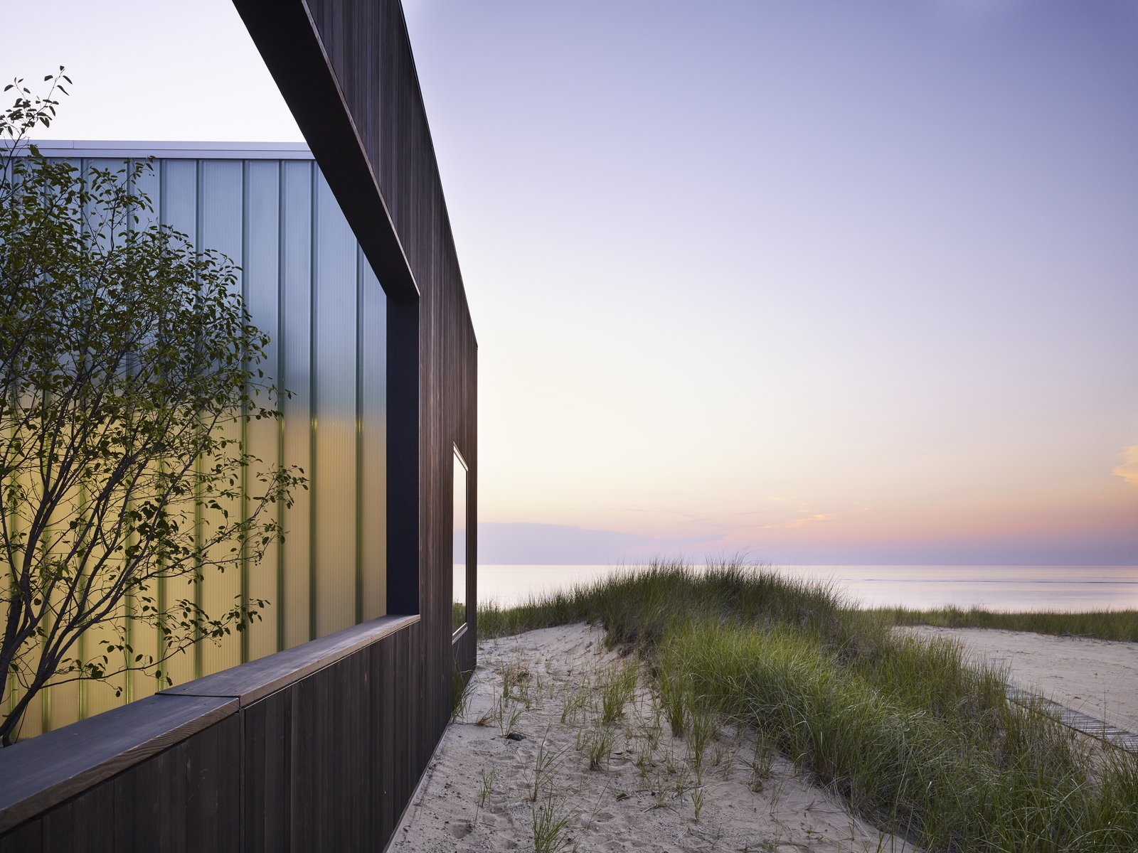 Exterior, House Building Type, Beach House Building Type, Wood Siding Material, and Flat RoofLine Here is a look at the colors of the beach at dusk against the charred timber exterior.     Photo 11 of 12 in Four Courtyards Form This Modern Waterfront Home