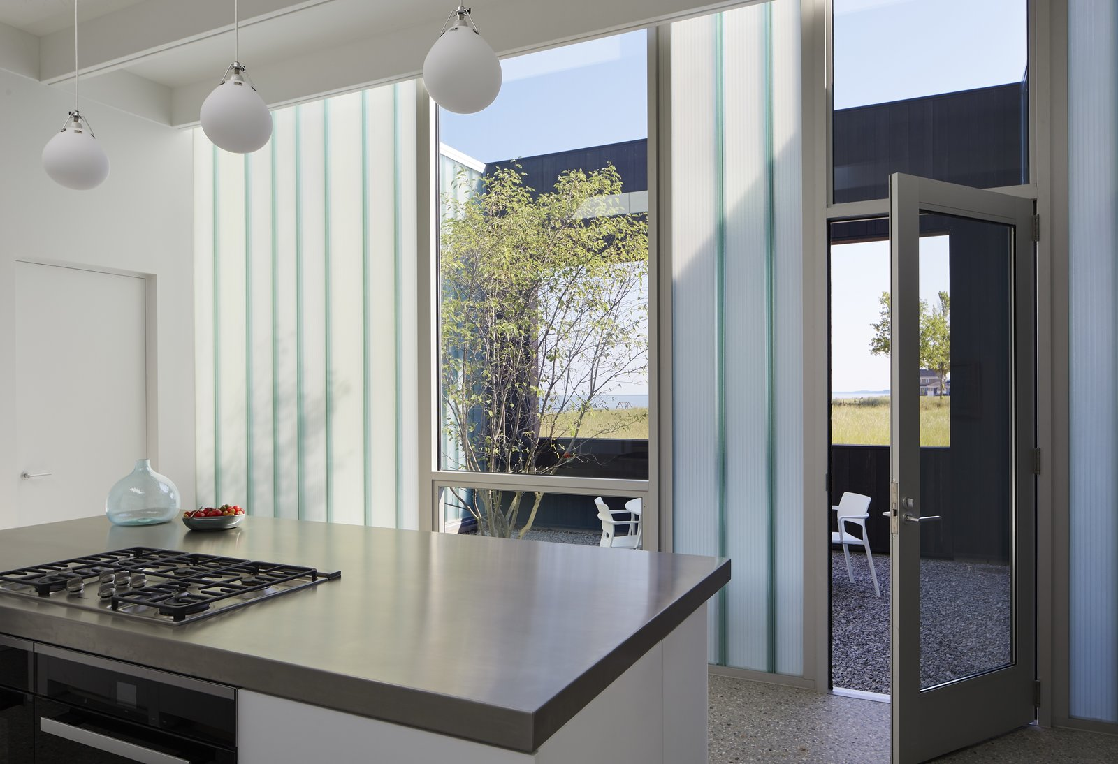 Kitchen, Pendant, Metal, Wall Oven, and Cooktops Directly east of the kitchen is a dining courtyard, which receives beautiful morning sunlight. This area is also shaded from the western sun in the late afternoon.    Best Kitchen Metal Range Photos from Four Courtyards Form This Modern Waterfront Home