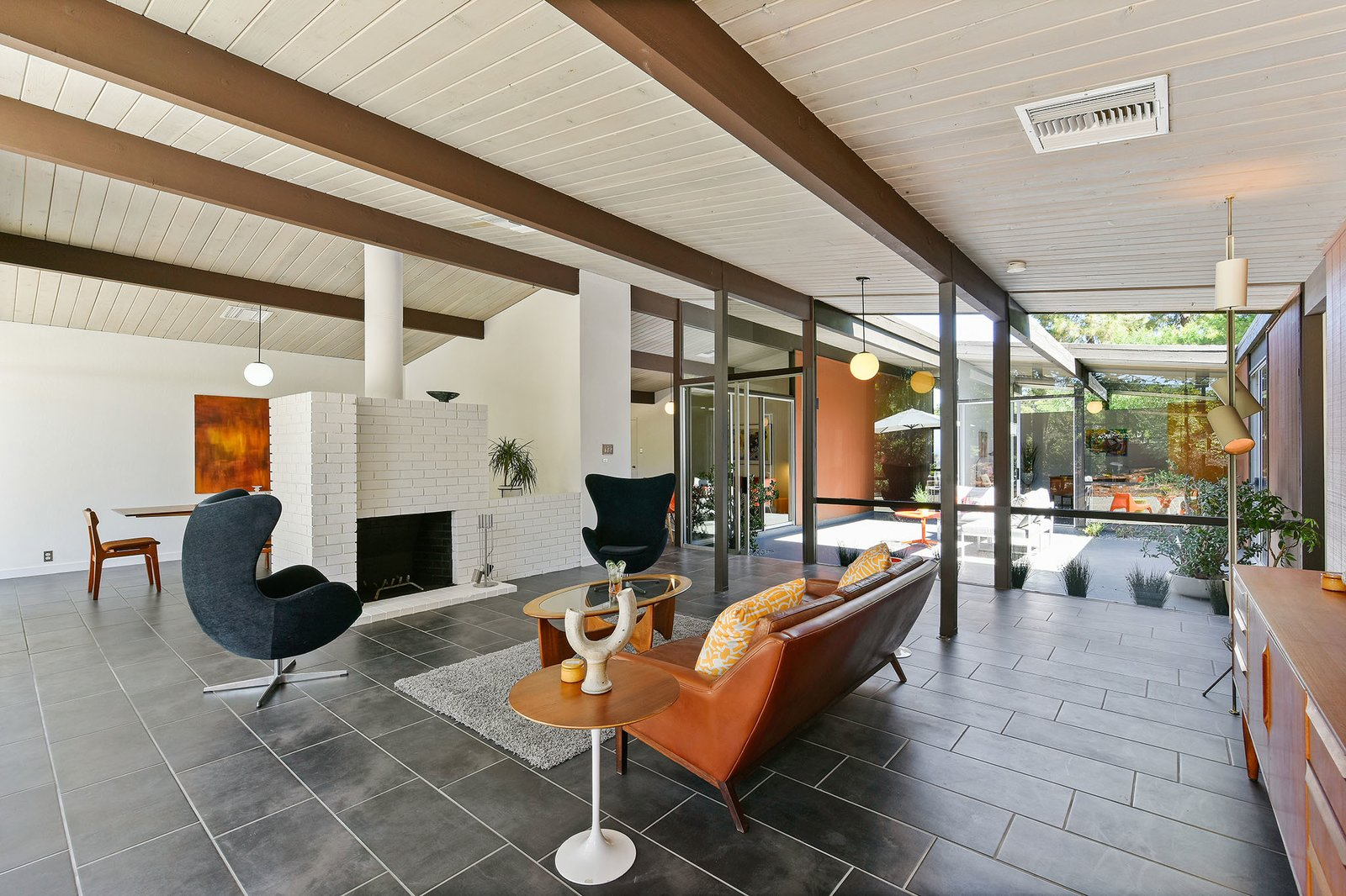 Living, Wood Burning, Porcelain Tile, Sofa, Coffee Tables, End Tables, Pendant, Chair, and Rug The expansive open-plan living area is also bright and airy.     Living Porcelain Tile End Tables Photos from A Bright and Breezy Eichler Hits the Market at $1.45M in California