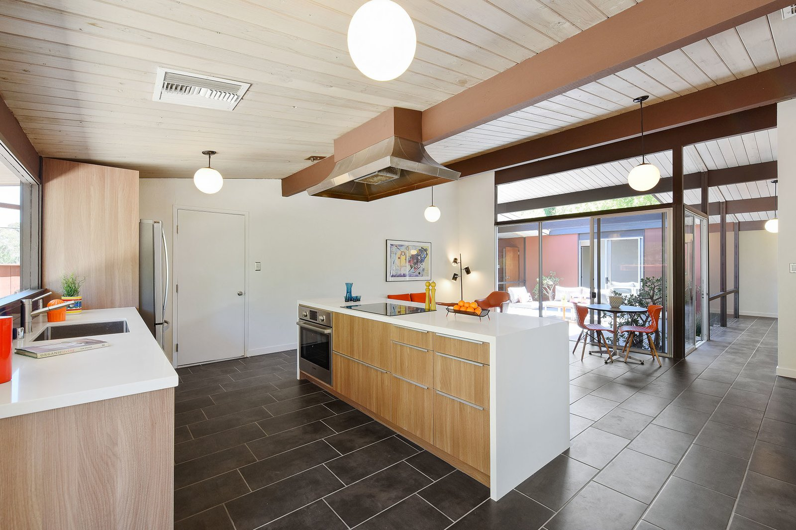 Kitchen, Drop In, Cooktops, Wood, Porcelain Tile, Pendant, Range Hood, and Wall Oven There is new porcelain tile flooring throughout.     Best Kitchen Pendant Range Hood Porcelain Tile Wood Photos from A Bright and Breezy Eichler Hits the Market at $1.45M in California