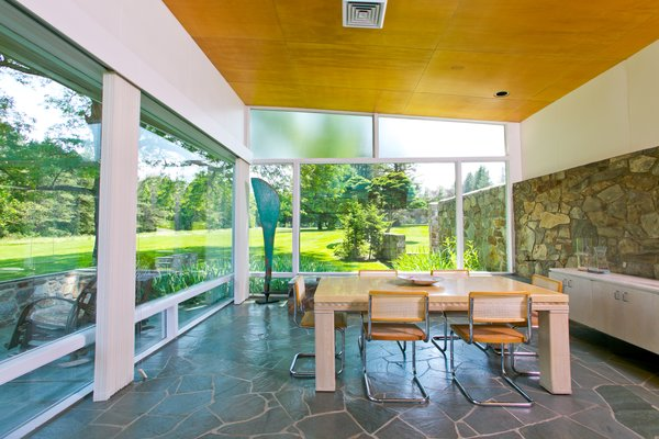 The dining area is surrounded by expansive glazing, with a stone wall that extends from the interiors straight outside the home.