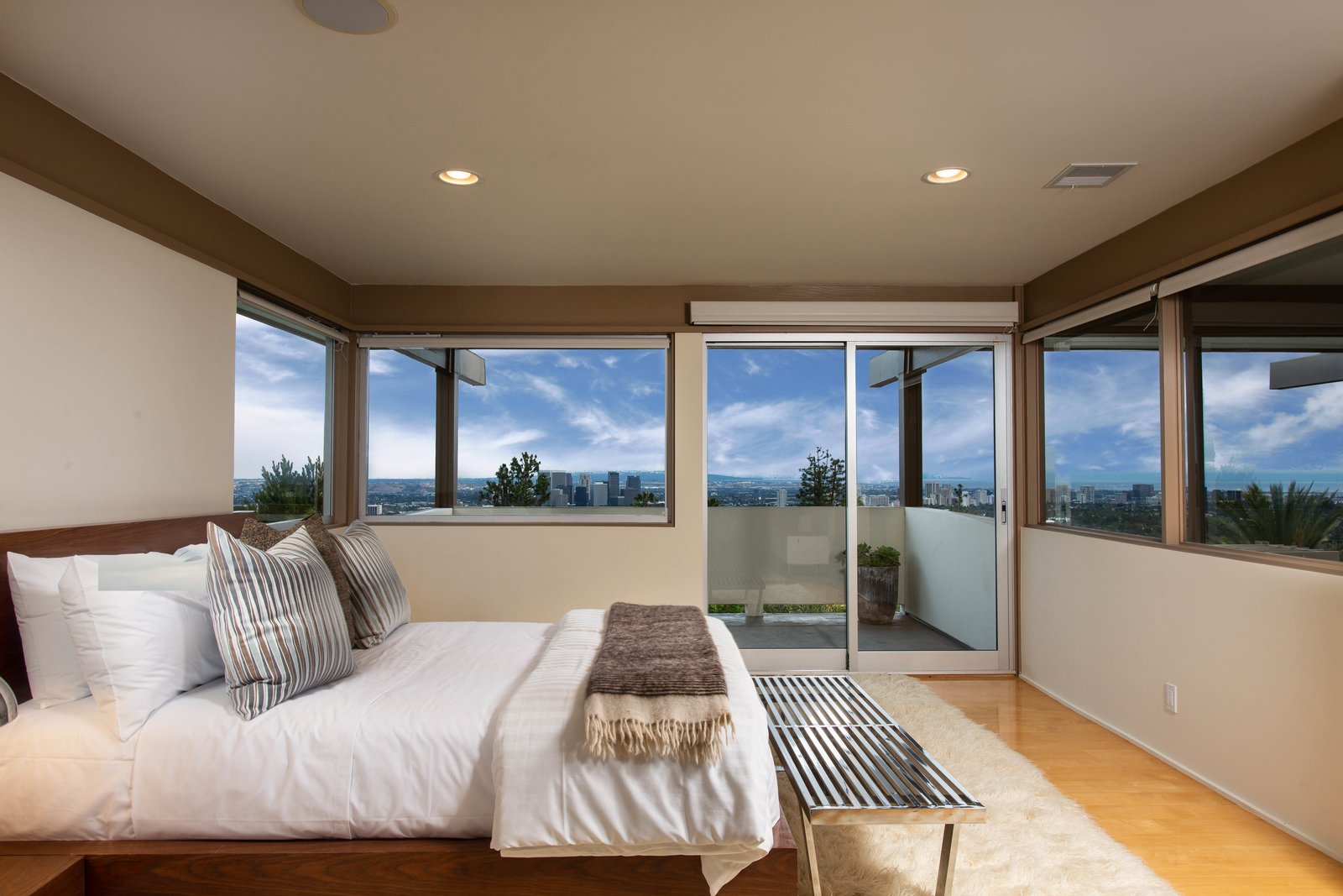 Bedroom, Bed, Recessed, Light Hardwood, Rug, and Bench The master is wrapped by panoramic views of downtown L.A. and the surrounding sea.    Best Bedroom Recessed Light Hardwood Bench Photos from A Widely Published Midcentury in L.A. Hits the Market at $6.9M