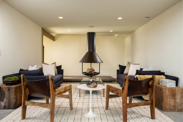 A cozy den with an original fireplace sits just off the kitchen. The fireplace, which appears in photographs taken by Shulman, originally had a two-story tall flue and was suspended from chains. Now, it sits securely on a stone platform and the flue ends at the first-floor ceiling.