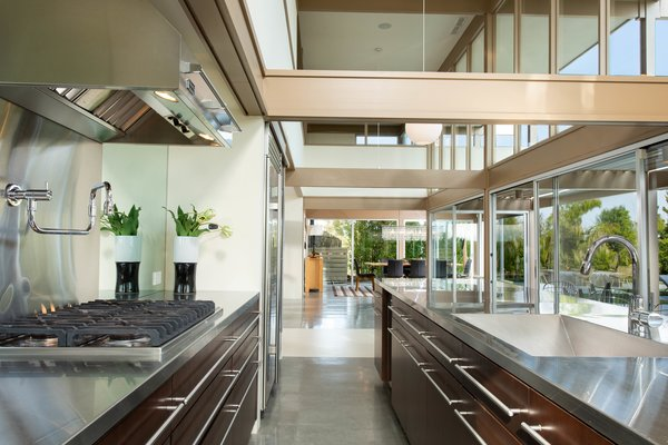 The open kitchen is bright and airy thanks to double-height ceilings, a wall of windows, and classic post-and-beam construction.