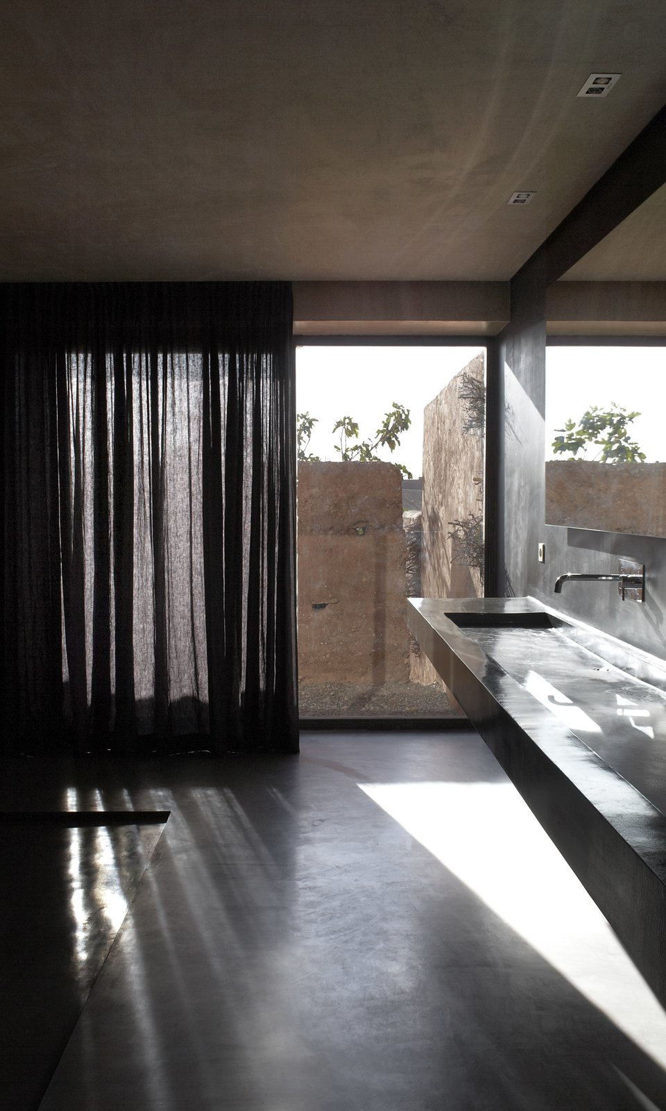 Bath Room, Wall Mount Sink, Drop In Sink, and Concrete Floor Floor-to-ceiling glass doors frame the gorgeous outdoor views.     Photo 4 of 8 in Soak Up the Sun at This Spectacular Moroccan Retreat