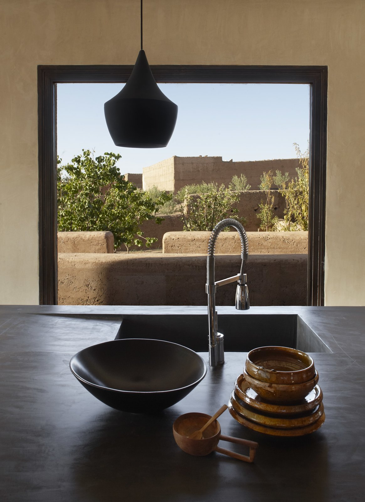 Kitchen, Drop In Sink, and Pendant Lighting The villa features striking minimalist interiors. Thanks to multiple expansive windows, natural light is able to pour inside, creating a bright, airy vibe.     Photo 3 of 8 in Soak Up the Sun at This Spectacular Moroccan Retreat