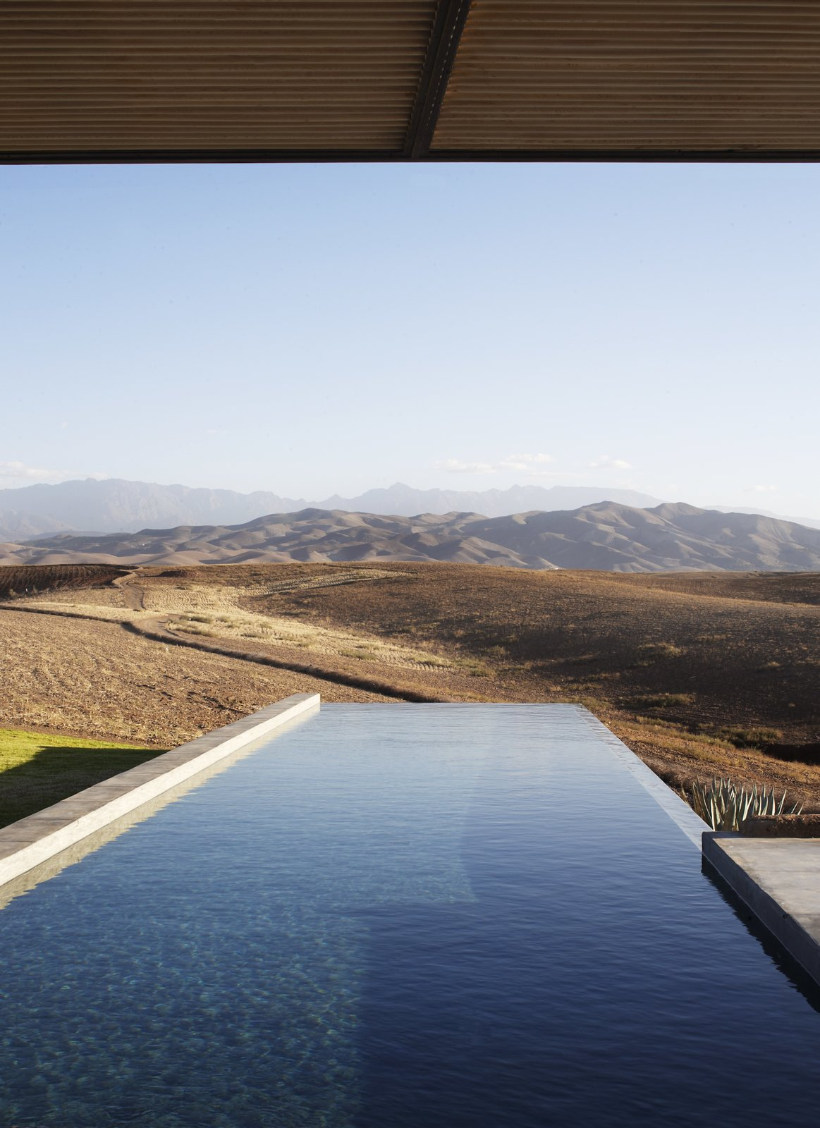 Outdoor, Back Yard, Infinity Pools, Tubs, Shower, and Concrete Pools, Tubs, Shower A rectangular infinity pool is set perpendicular to the facade, making it the perfect spot for cooling off in the Moroccan heat.    Photo 6 of 8 in Soak Up the Sun at This Spectacular Moroccan Retreat