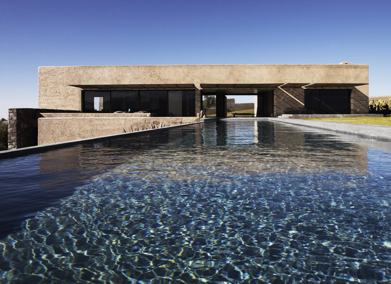 Outdoor, Back Yard, Large Pools, Tubs, Shower, Infinity Pools, Tubs, Shower, Grass, and Concrete Pools, Tubs, Shower A view of the villa from the edge of the pool.     Photo 8 of 8 in Soak Up the Sun at This Spectacular Moroccan Retreat