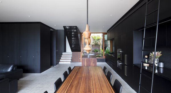 An overview of the first-floor living space. Despite the dark color palette, the home is still able to find plenty of light with the full-height sliding doors.