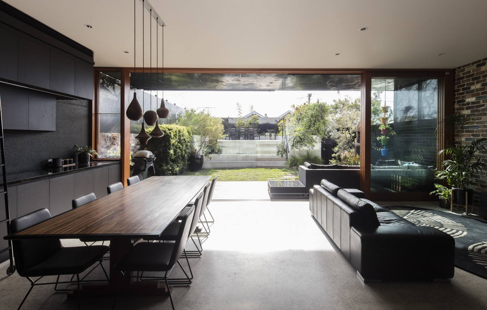 Living, Table, Storage, Chair, Sofa, Concrete, Pendant, Recessed, and Rug The view out to the garden.  Living Storage Pendant Concrete Photos from A Dark Sydney Home Finds Light With a Unifying Expansion