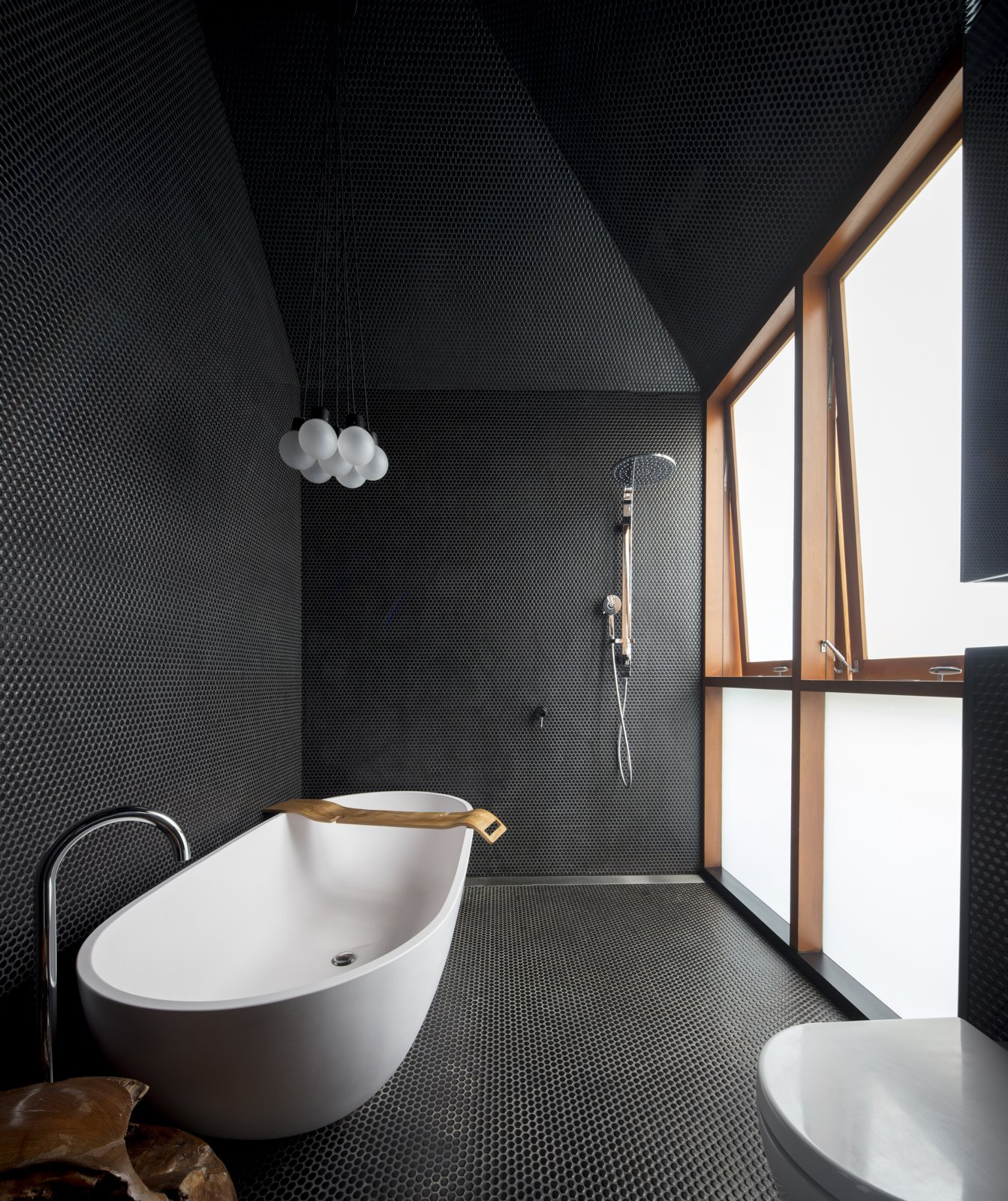 Bath, Freestanding, Open, Pendant, Porcelain Tile, Mosaic Tile, and One Piece The bathroom continues the black perforated theme, and features an asymmetric pitched roof.    Bath Mosaic Tile One Piece Open Photos from A Dark Sydney Home Finds Light With a Unifying Expansion