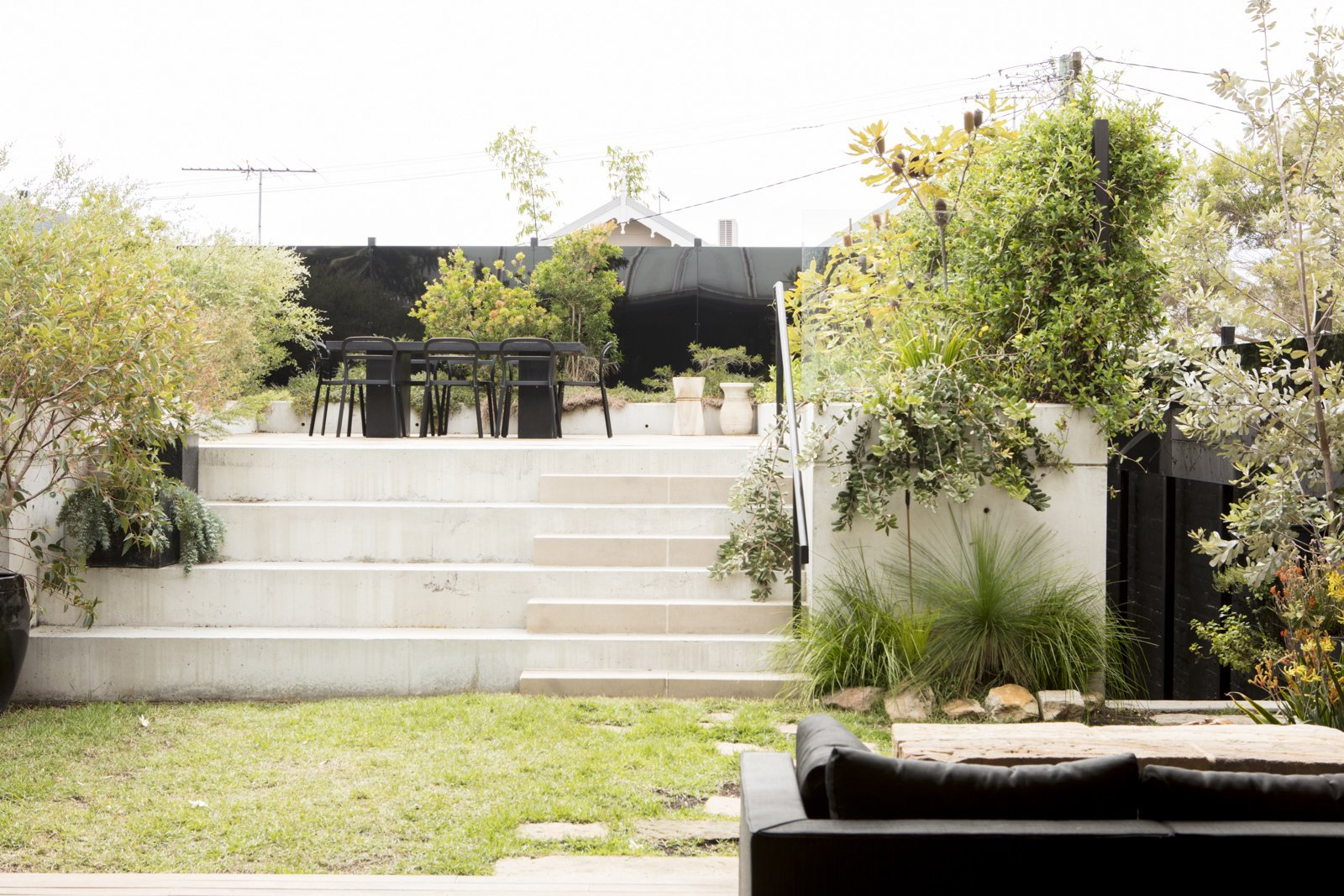 Outdoor, Back Yard, Horizontal Fences, Wall, Gardens, Trees, Grass, and Small Patio, Porch, Deck The addition of black metal perforated screens along the perimeter of the garden provide privacy and light, without appearing to be too austere.    Photo 1 of 9 in A Dark Sydney Home Finds Light With a Unifying Expansion
