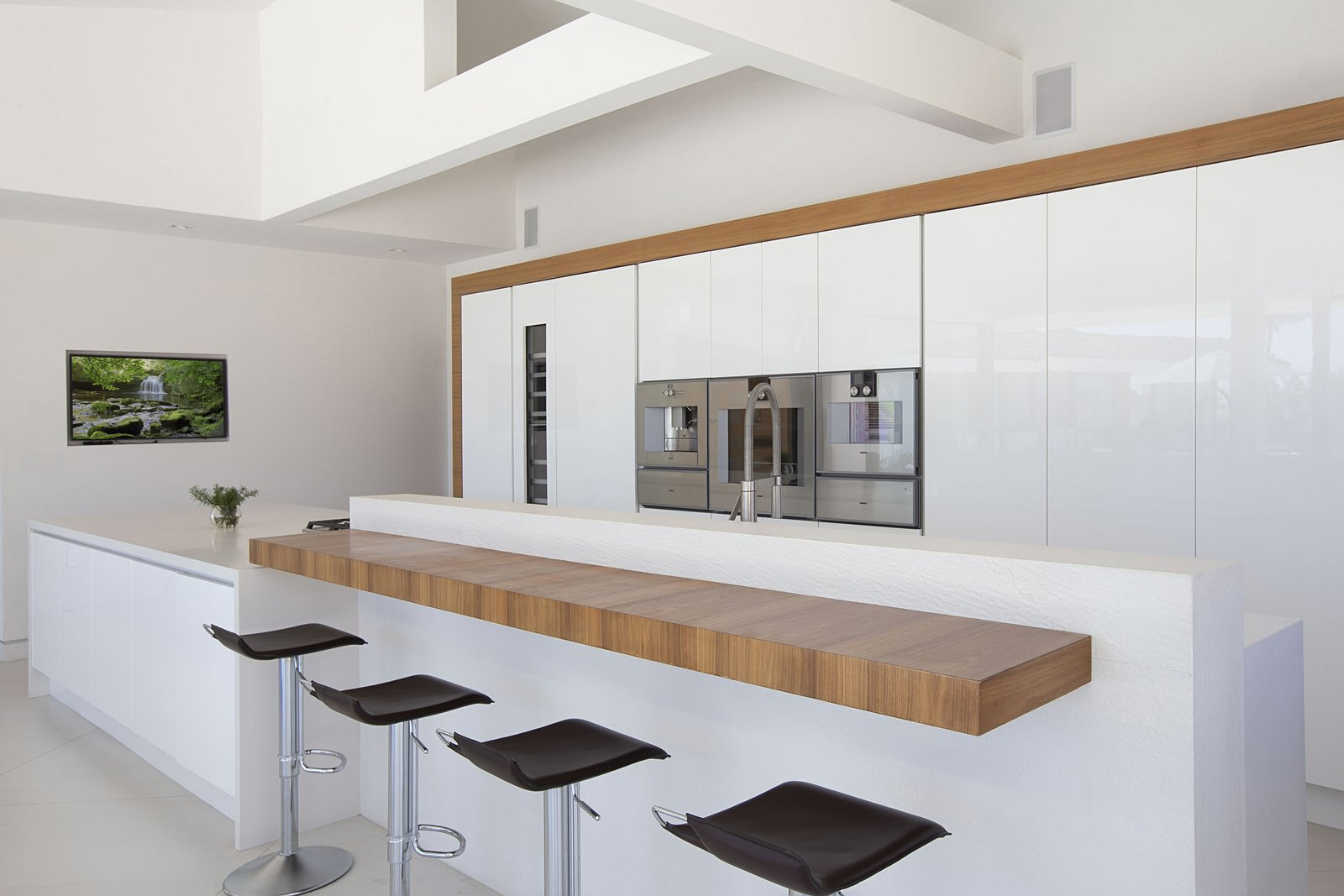 Kitchen, Refrigerator, Ceramic Tile, White, Wall Oven, Range, Wine Cooler, and Quartzite Aster Cucine's eco-friendly cabinetry from Italy was chosen along with high-end, efficient appliances and fixtures.  Best Kitchen Ceramic Tile Refrigerator Photos from A Renovated Midcentury in San Diego Is Sharp and Sustainable