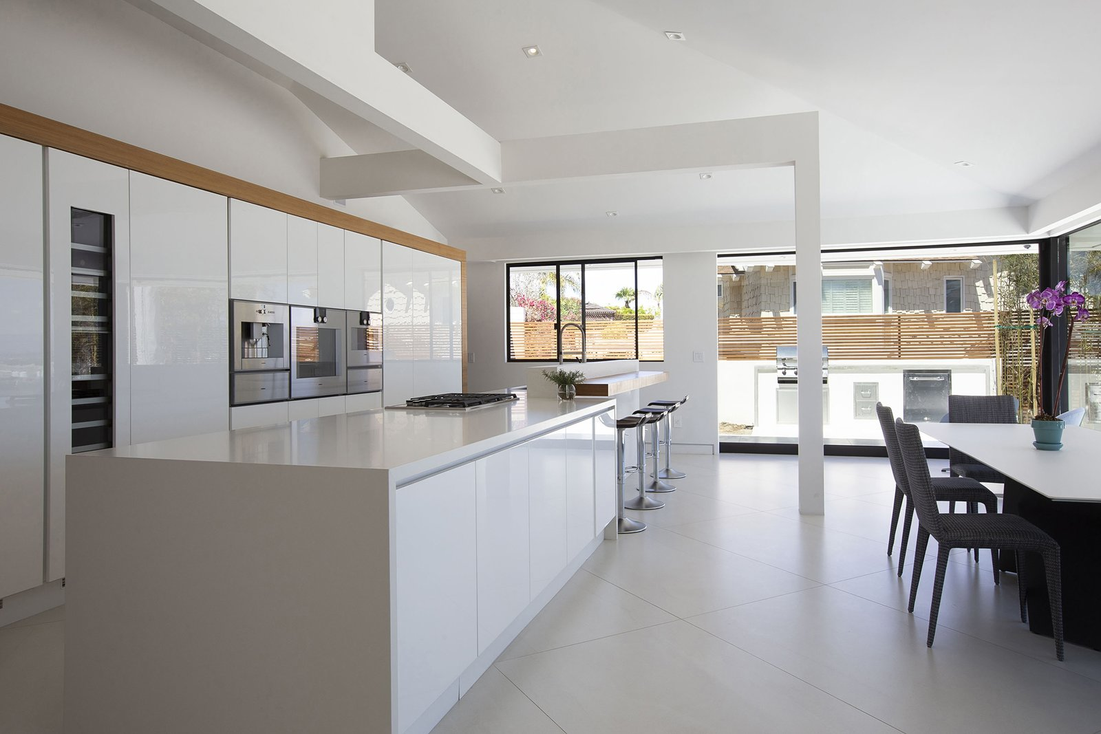 Kitchen, Microwave, White, Range, Quartzite, Wall Oven, Recessed, Ceramic Tile, and Wine Cooler The open kitchen/dining room is bright and airy.  Best Kitchen Microwave Wine Cooler White Photos from A Renovated Midcentury in San Diego Is Sharp and Sustainable