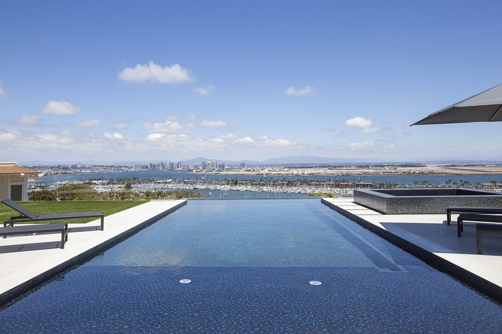 Outdoor, Large, Side Yard, Large, Walkways, Infinity, and Grass The infinity pool overlooks stunning views of Mexico and the San Diego skyline and harbor.  Best Outdoor Large Side Yard Photos from A Renovated Midcentury in San Diego Is Sharp and Sustainable