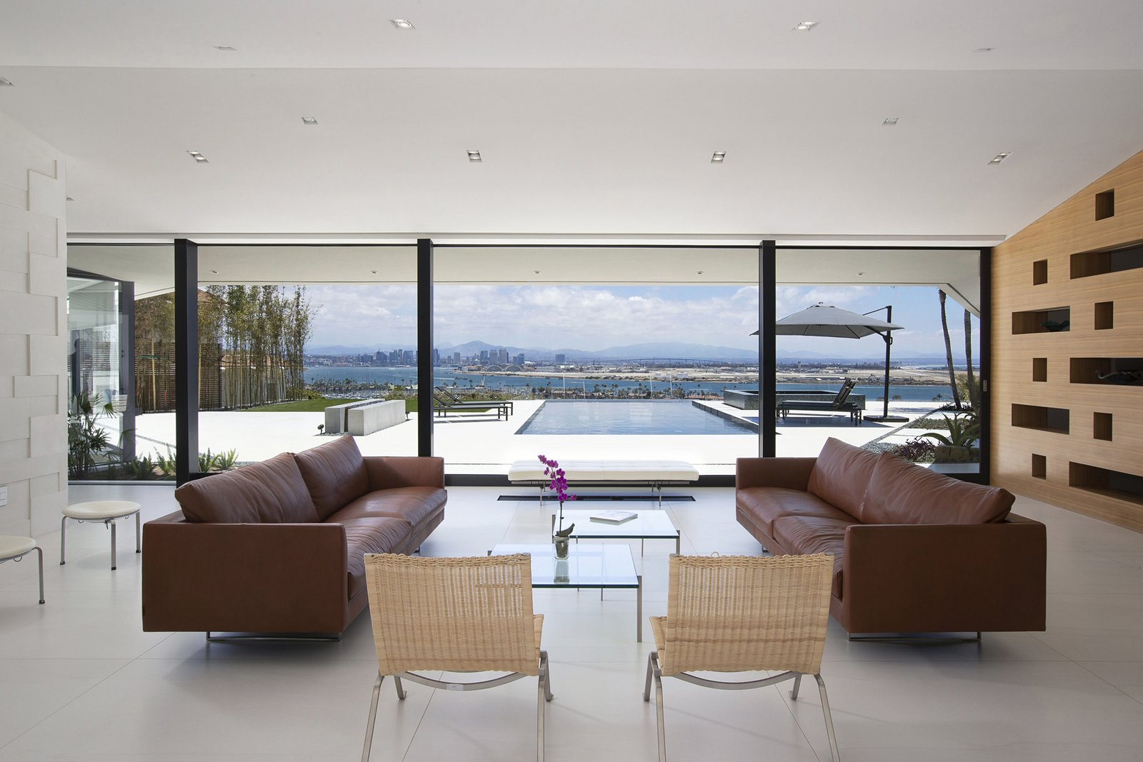 Living Room, Sofa, Stools, Recessed Lighting, Coffee Tables, Ceramic Tile Floor, Chair, and Bench The living room features stunning views of the infinity pool and beyond.  Best Photos from A Renovated Midcentury in San Diego Is Sharp and Sustainable