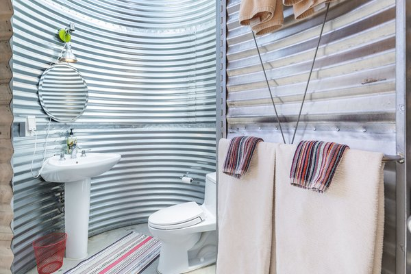 The bathroom is located inside the duct-like cylinder of corrugated aluminum.