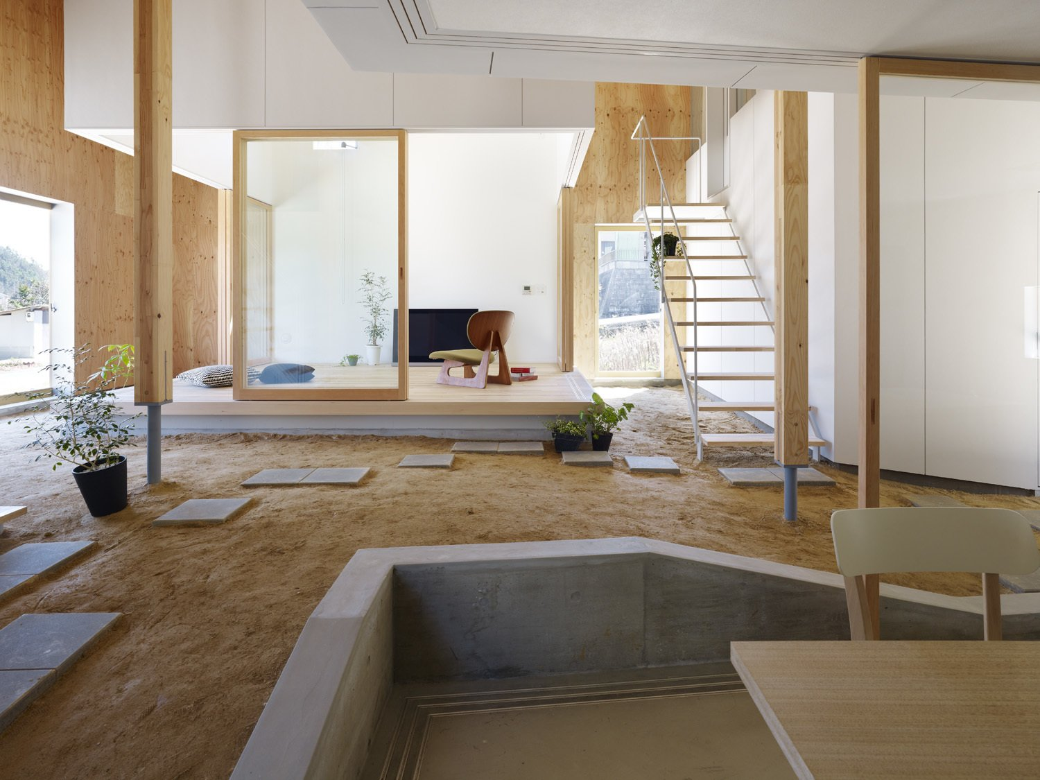 Living, Chair, Table, Light Hardwood, and Concrete The new space truly reimagines what indoor and outdoor space really is.   Best Living Concrete Light Hardwood Photos from A Dirt Floor Snakes Through This Spectacular Japanese House