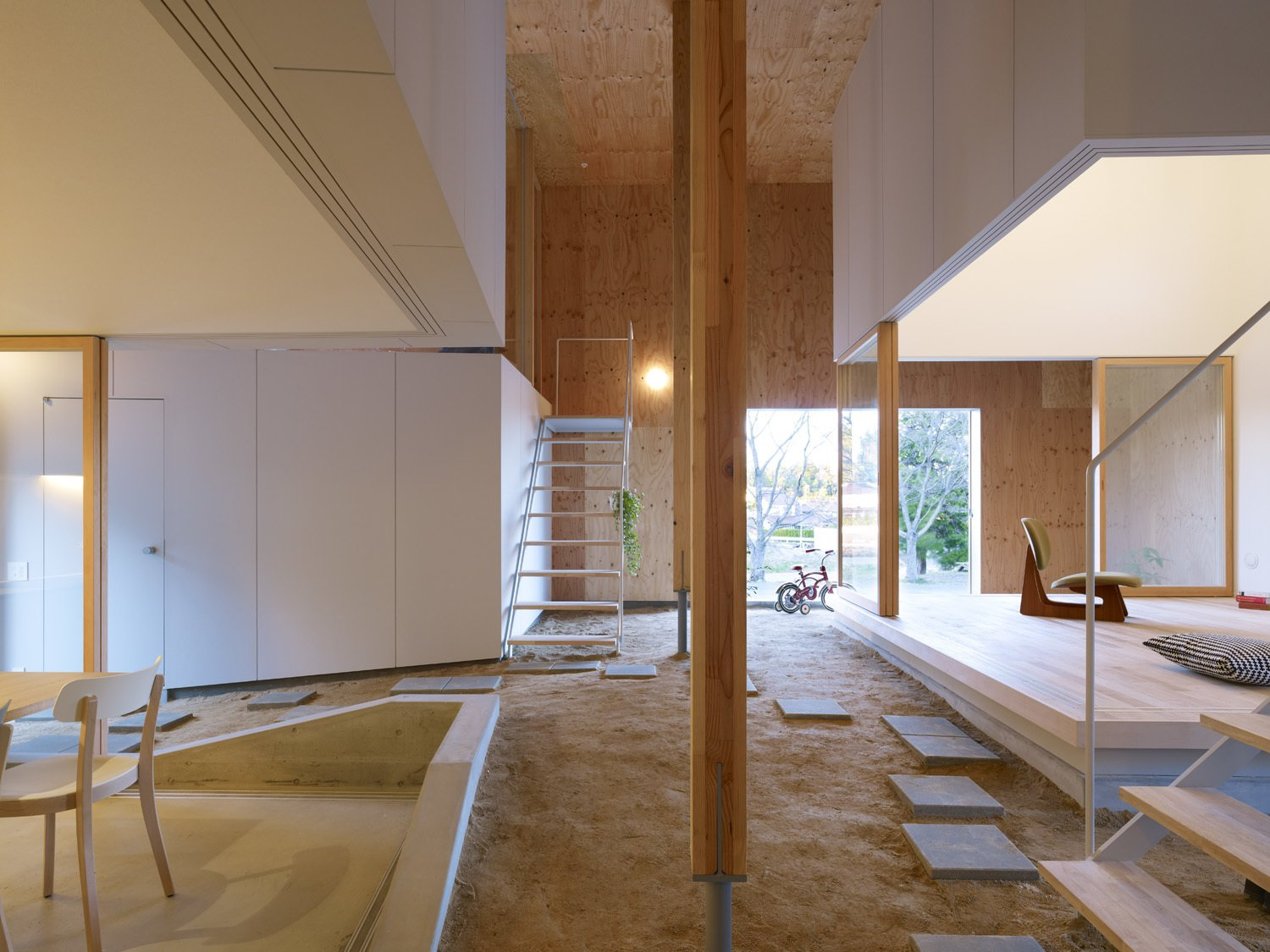 """Staircase, Metal Railing, and Wood Tread """"By taking in the slope into the building and creating a sloped 'doma' area, it was possible to bring the outside into the building,"""" say the architects.   Photos from A Dirt Floor Snakes Through This Spectacular Japanese House"""