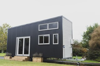 The outside of the tiny home is sheathed in two-tone corrugated metal and a slanted roof. This sleek, modern look is inspired by the company's earlier model, the Millennial Tiny House.