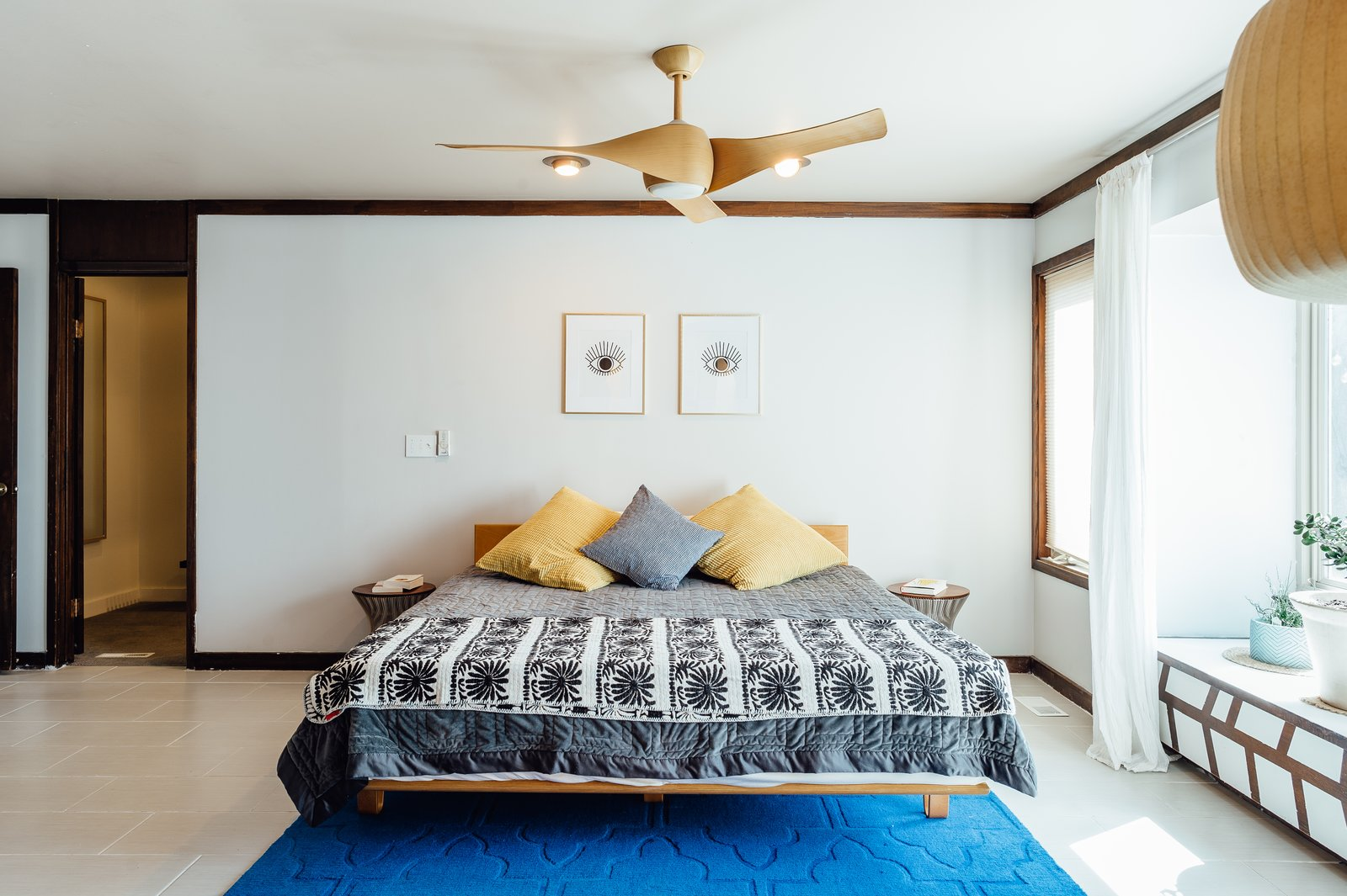 midcentury bedroom with ceiling fan and light and two accent ceiling recessed lights above bed