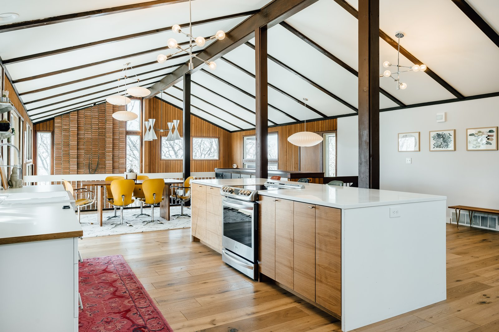 Kitchen, Light Hardwood, Range, Wood, Pendant, Quartzite, Rug, White, and Drop In The home possesses an authentic midcentury vibe with period-appropriate, contemporary updates.  Best Kitchen Pendant Rug Photos from A Midcentury Gem in Utah Is Listed For $550K