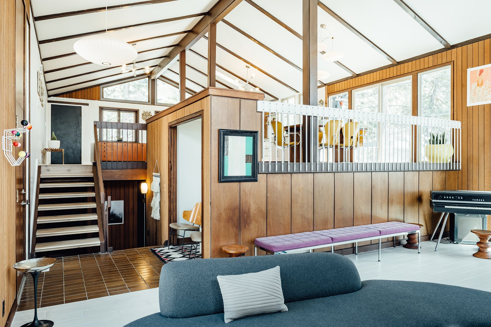 Living Room, Bench, Pendant Lighting, Porcelain Tile Floor, and Sofa The 4,312-square-foot home is spread over multiple levels.  Photo 6 of 12 in A Midcentury Gem in Utah Is Listed For $550K