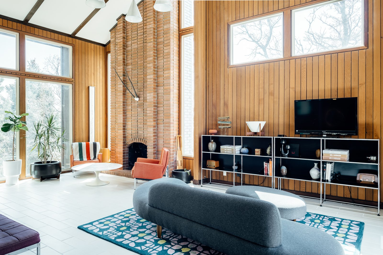 Living, Porcelain Tile, Chair, Rug, Coffee Tables, Pendant, Bookcase, Sofa, and Standard Layout High ceilings and a full-length brick fireplace are complemented by extensive glazing.  Best Living Porcelain Tile Standard Layout Photos from A Midcentury Gem in Utah Is Listed For $550K